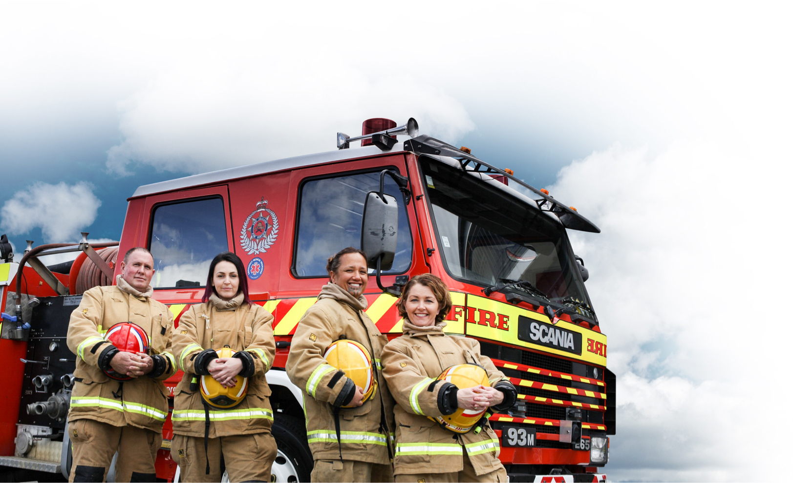 Group of firefighters in full kit standing in front of a fire engine
