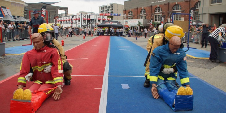 Two firefighters in full kit dragging dummies